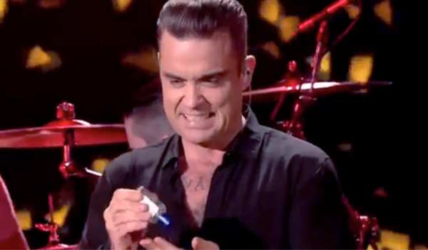 Robbie Williams tocca i fan e si disinfetta le mani