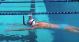 Campionessa olimpica nuota con un bicchiere di latte sulla testa